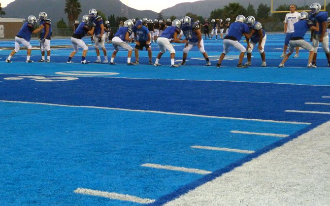 West Hills lineman perform a drill on the blue turf