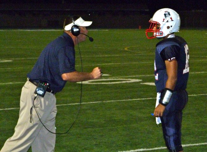 Christian offensive coordinator David Beezer gives the play call to Patriots junior quarterback Michael Carrillo