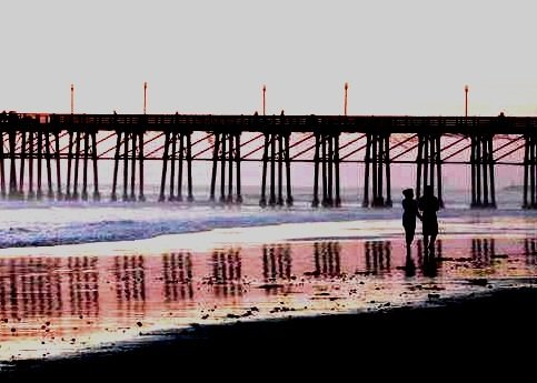 Oceanside pier at sunset as couple walks by.