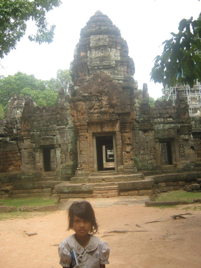 A Cambodian girl stands proudly in front of an Angkor temple.