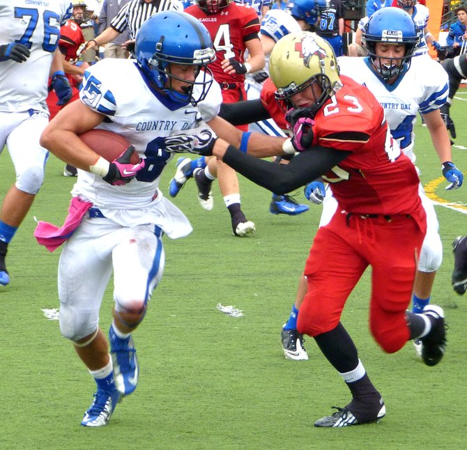 La Jolla Country Day senior running back Sage Burmeister applies a stiff arm in an attempt to break free from Santa Fe Christian senior defensive back Nathan Ross