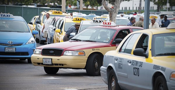 Taxis queue up at a holding lot near Lindbergh Field.