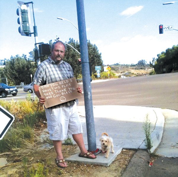 Shawn M. (with his dog Boo) solicits money to replace his car's tires.