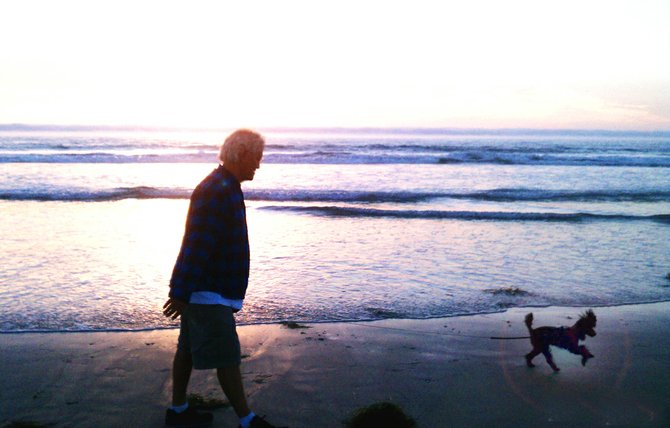 A man and his best friend walk the sands of Mission Beach