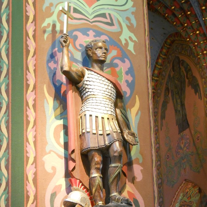 Saint Expeditus / Ekspedyt or Wierzyn in the St. Adalbert Church in Poznan (Saint Adalbert Hill). In the 20th century Pr. Boleslaus Koscielski (pastor in the years 1903-1925) contributed considerably to the present interior appearance. The church had got a new modernistic decor dominated by rich rhythmic folk art-inspired murals with the Our Lady, St. Adalbert, and St. Stanislaus images, including the 'Bogurodzica' (historic, Polish national anthem) text fragments intertwined with the ornaments painted by Anthony Procajlowicz. In the 17th century both the nave and the chancel were elevated, and then the stellar vaulting was built (renaissance forms with columns). St. Expeditus (the statue in the picture), invoked for urgent and hopeless causes especially as the eleventh hour (by soldiers and unemployed people; implored for success in lawsuits, sufferings, storms, fires, floods, losses, and epidemics; in the case of family disputes, for the sinners conversion, and in financial difficulty), was made the patron saint of dealers, sailors, students, and examinees. He is considered to be the best advocate for jobseekers. The sacred art depicts him as a soldier saint.