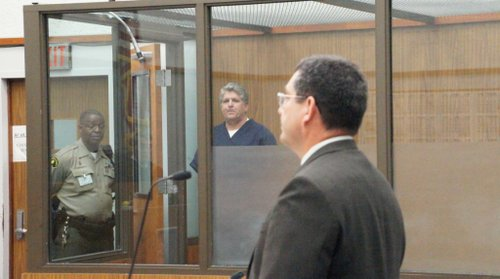 Pines in the holding tank, prosecutor James Romo in foreground. Photo Weatherston