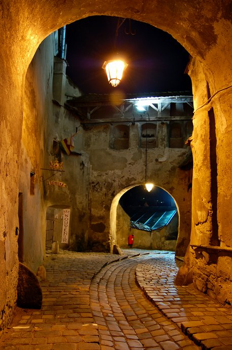 A winding cobblestone pathway underneath Sighişoara's 13th-century Clock Tower.