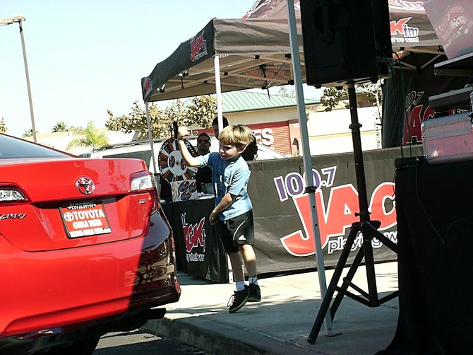 Duggan-kid power dancing in Mission Valley before his Papa won a 36-month lease to a 2013 Kia Optima SX.