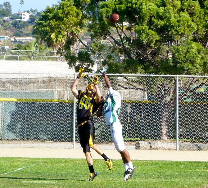 Mission Bay senior receiver Kelly Weese goes up for the ball alongside Coronado senior defensive back Tyree Johnson on a deep pass