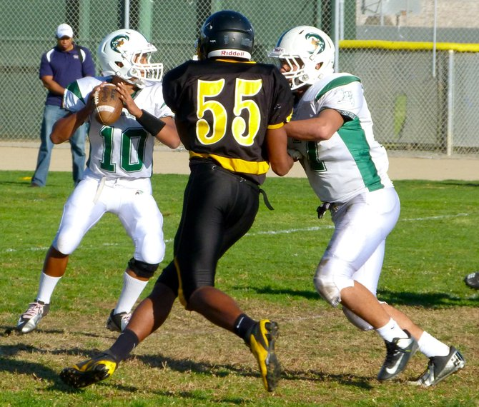 Coronado sophomore quarterback Francis Pugeda drops back to pass with Mission Bay senior defensive end Aaron Cobbler applying pressure