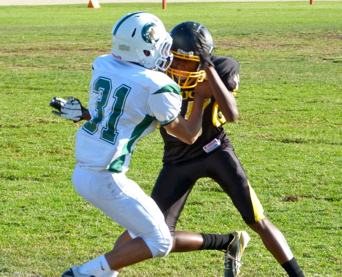 Mission Bay junior receiver Shaki Harvey gets tangled up with Coronado junior defensive back Gabe Granados on the outside