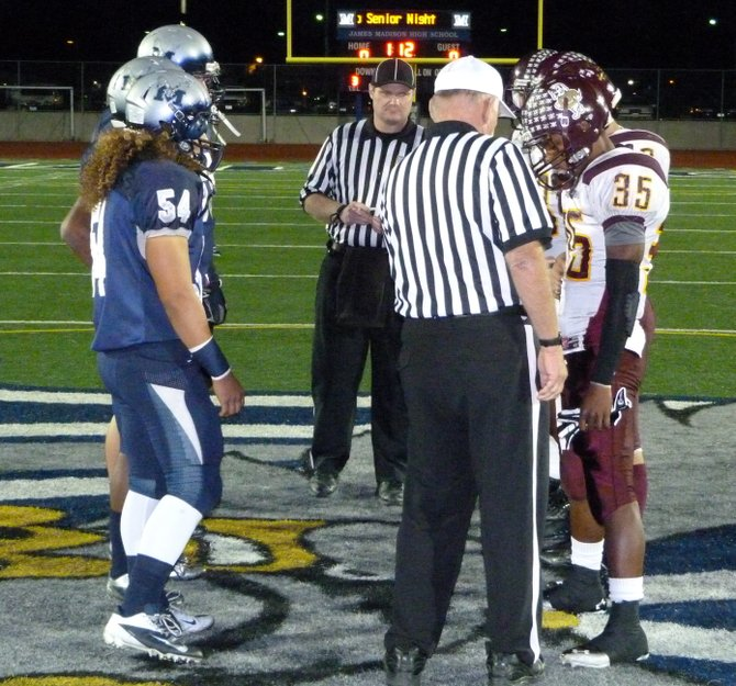 Madison and Point Loma team captains meet at midfield for the coin toss