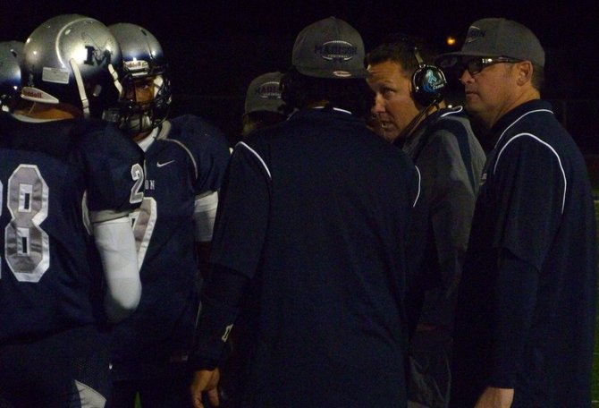 Madison players and assistant coaches huddle up around Warhawks head coach Rick Jackson (headset) during a timeout