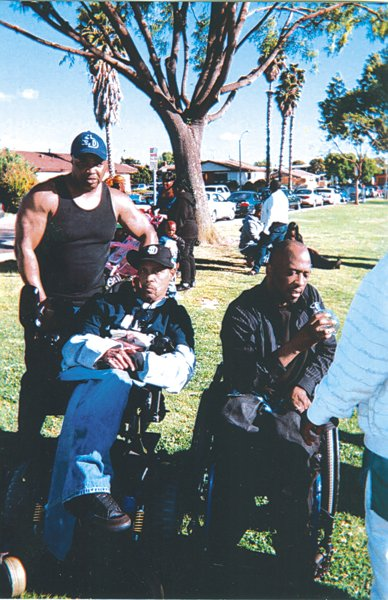 The author, standing, with two former gang members at a 2010 reunion. Both are paralyzed as a result of gun wounds.