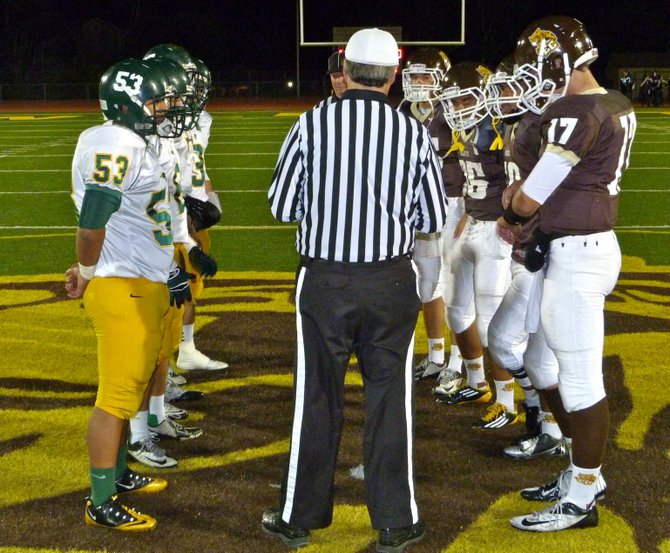 Patrick Henry and El Camino team captains meet at midfield for the coin toss