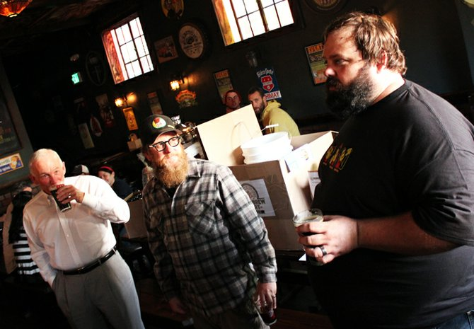 Sanders sips a Jerry's Farewell alongside Monkey Paw Pub & Brewery owner Scot Blair while listening his brewing partner Derek Freese talk about the beer