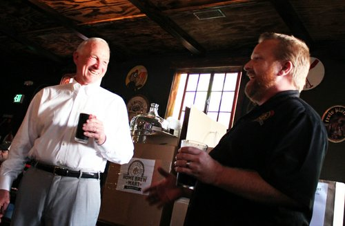 Ballast Point specialty brewer and former president of the San Diego Brewers Guild, Colby Chandler presents Sanders with a kit from Home Brew Mart