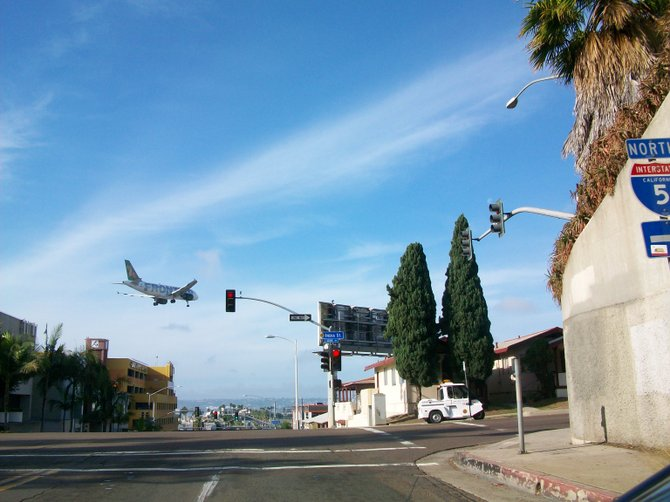 Frontier Airlines descending over India Street in Little Italy.