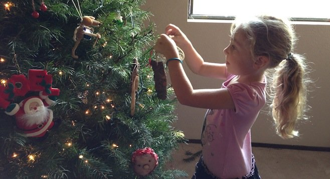 Olivia carefully arranges an ornament