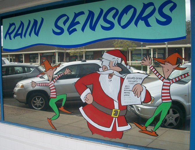 Santa seems really excited to give out sprinkler heads on the Hydro-scape landscaping company's window in Encinitas.