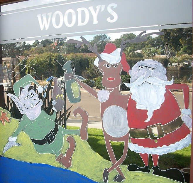 At Woody's Solana Beach, Santa appears drunk. Employee Jessica Shrader painted two window scenes on the Coast Hwy. bar and restaurant.