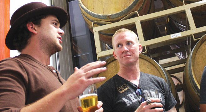 Societe Brewing Company's Doug Constantiner shows a customer around the company's newly installed barrel house.
