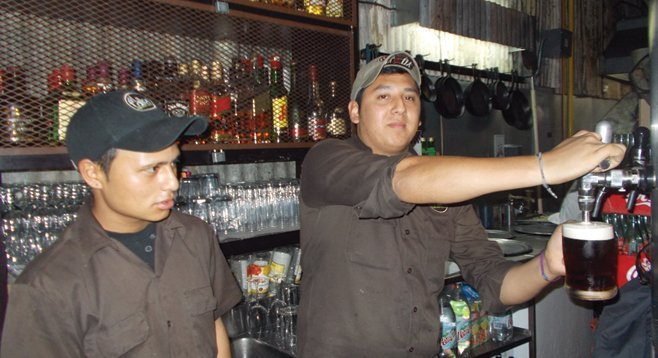 Barkeeps pull a couple of pints of Baja-brewed beer.