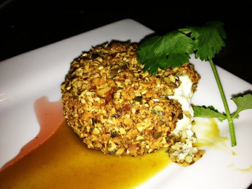 Pepita- and almond-crusted goat cheese with chipotle syrup and jamaica reduction