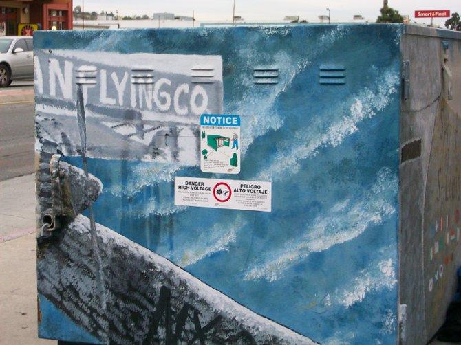 Aviation-themed utility box art along Midway Drive near the Chevron gas station.