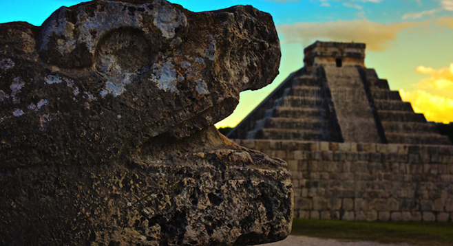 "Kukulkan Pyramid (""El Castillo"") with a stone serpent in the foreground."
