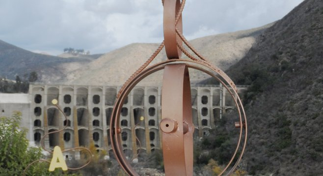 Through this pipe scope atop a rattlesnake-shaped rock wall, one can pinpoint features of Lake Hodges Dam.