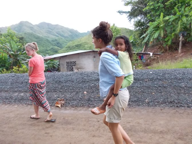 Volunnteers, Madeline Taylor and Angela Stern, walk through the community of La Chumicosa with their new friend Marisa.