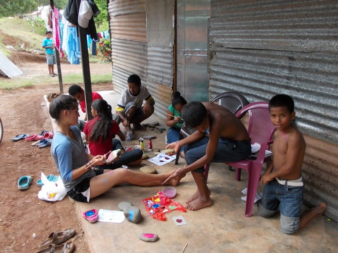 Community members of La Chumicosa and Hijo de Dios paint with volunteers in Coclé, Panama