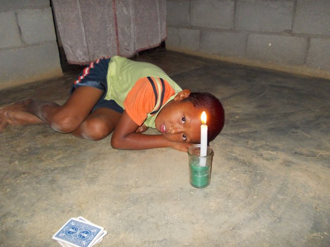 Ormelis lays in the candlelight after a game of cards with me. (Coclé, Panama)