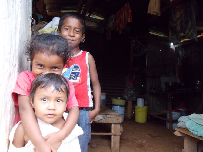 Brothers and sisters stand in the entryway of their home. (Coclé, Panama)
