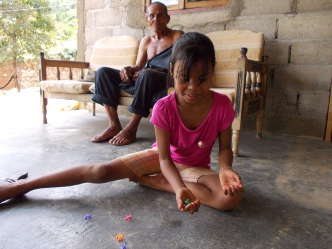 Mylane plays jacks at her grandpa's house. (Coclé, Panama)
