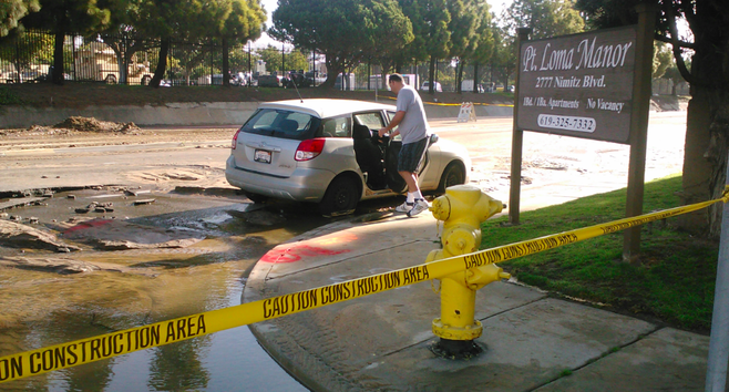 A Point Loma resident assesses damage to his car on Nimitz Boulevard