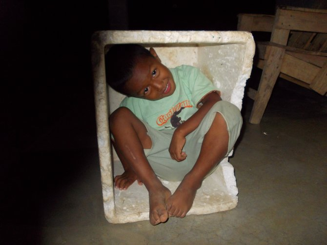 Angel playing in a box. Men from nearby cities ride in on motor cycles and sell fish out of these boxes. Cocle, Panama
