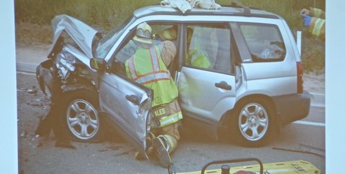 Evidence photo of emergency responders extricating a survivor from the smashed Subaru.