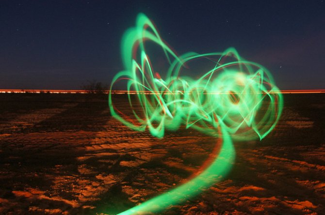 I took this during a trip to the Imperial Valley, CA Sand Dunes. We were camping in the flats in on the Buttercup Valley side of the I-8 FWY. Playing with shutter speed and ISO while swinging a couple glow sticks around gave me this beautiful shot. The light streak in back is the freeway and the glow is from the fire.