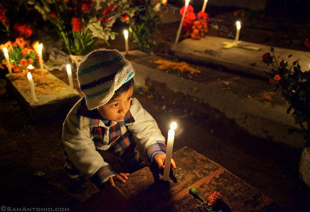 Little boy placing a candle on his deceased relative's grave at the Xoxocotlan Cemetery