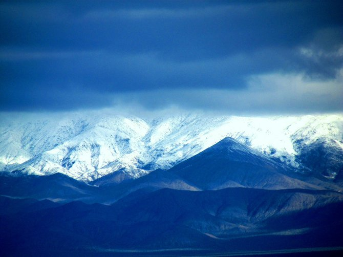 A snow-covered range climbs into the clouds.