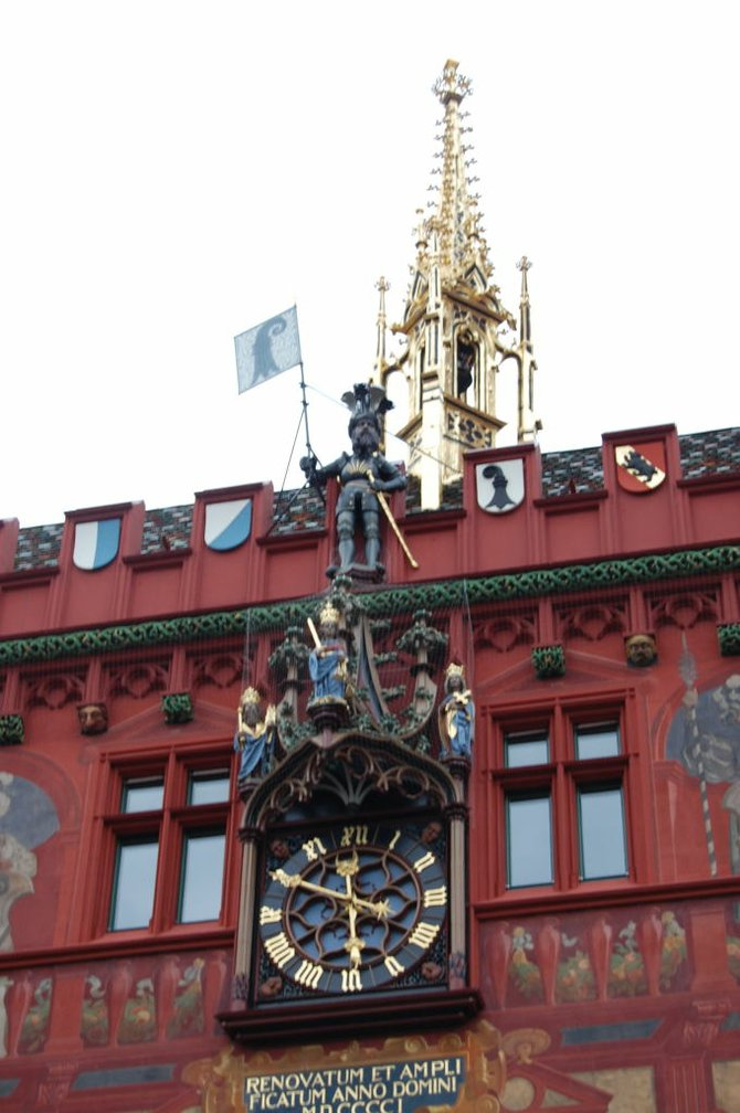 The clock at Basel's reddish Rathaus (city hall).