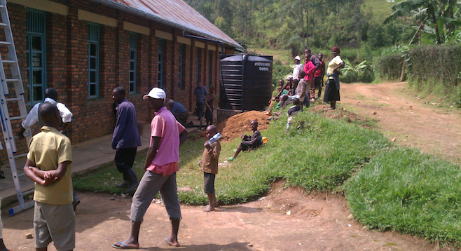 Rwandans gather to watch as the author and others install a rain harvest system on a Kibuye church.