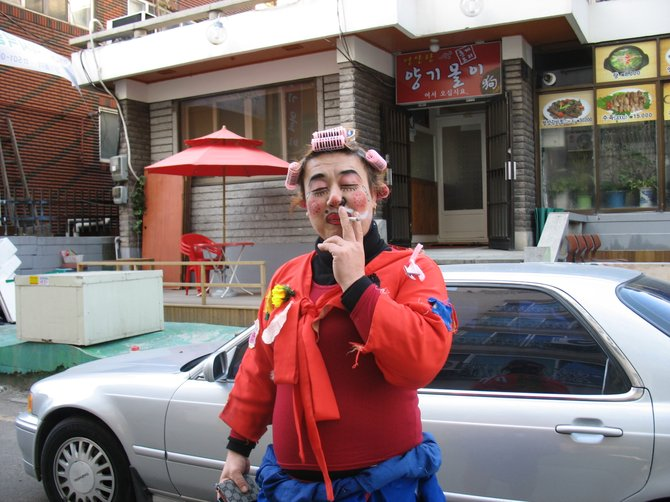 A clown smoking in front of his 원룸 / studio apartment in Bupyeong.