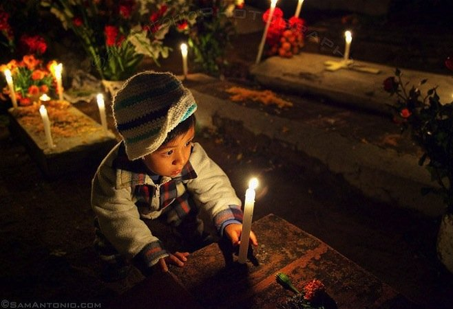 Little boy placing a candle on his deceased relative's grave at the Xoxocotlan Cemetery.