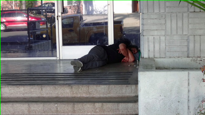 Homeless individuals sleep near the entrance and on the side of the building.