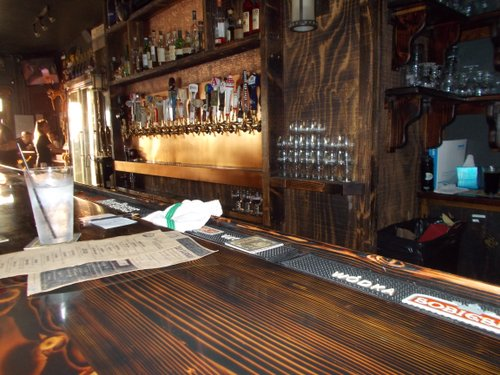 Monkeypaw's stained wood counter lights up at sunset