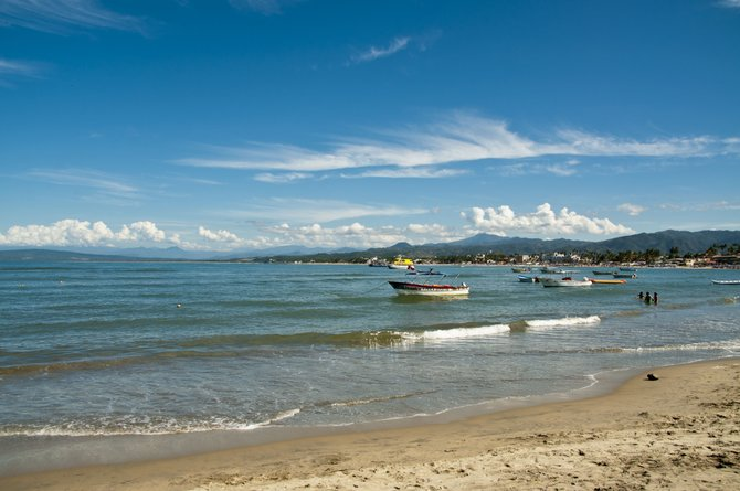 this is the beautiful beach of guayabitos,Nayarit ,Mex. here you can see the boats on the calm of the water and the people enjoy the warm waters.