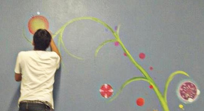 Escondido Arts Partnership artists paint a mural of the mandala tree at the Winter Shelter.